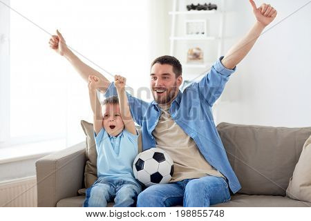 family, entertainment, sport and people concept - happy father and little son with ball watching football or soccer game tv at home stock photo