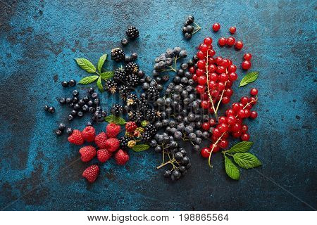 Assorted fresh berries with leaves on metal background. Mix of fresh berries with leaves on textured metal background.  stock photo