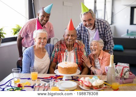 Portrait of cheerful senior people celebrating birthday at nursing home stock photo