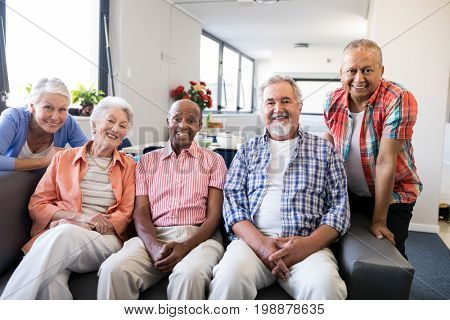 Portrait of multi-ethnic senior people sitting on couch at nursing home stock photo