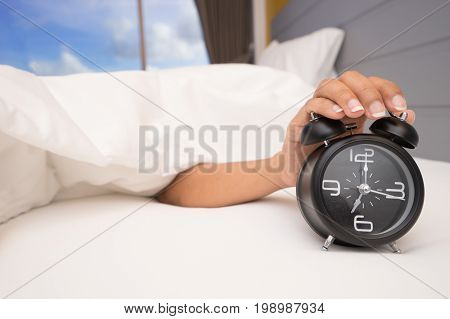 Hand under blanket reaching out for alarm clock, Closeup on woman hand reaching to turn off alarm clock, Selective focus stock photo