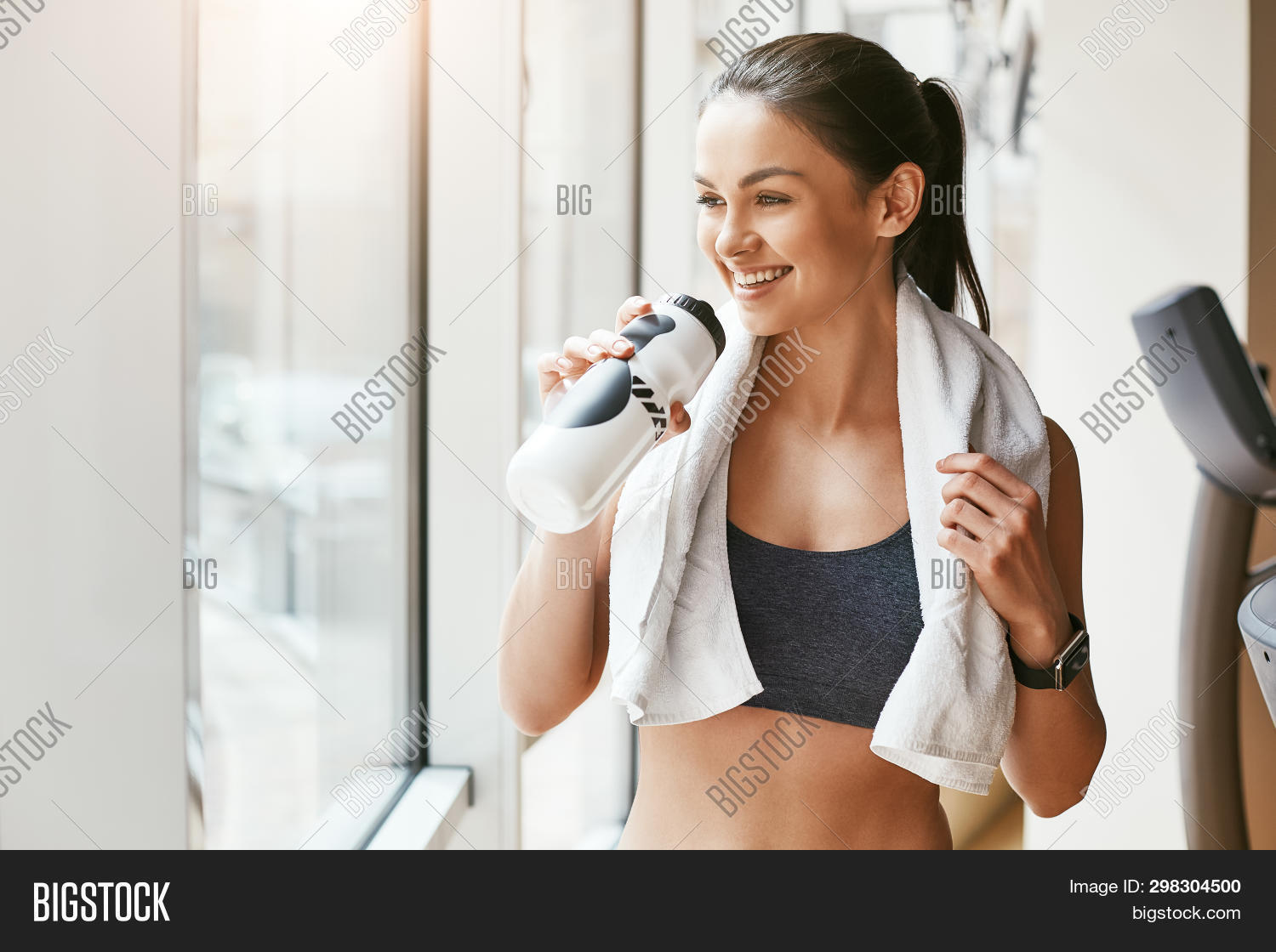 Time For Rest. Young And Cheerful Woman In Sportswear With White Towel On Her Shoulders Drinking Wat