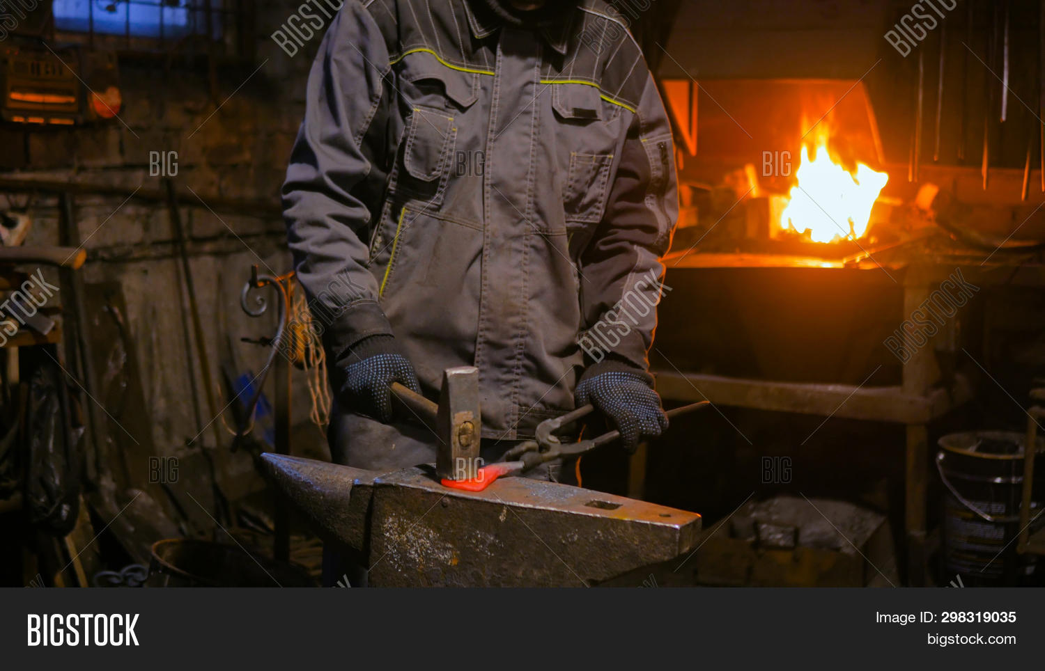 Professional Blacksmith Working With Metal On Anvil At Forge, Workshop. Handmade, Craftsmanship And