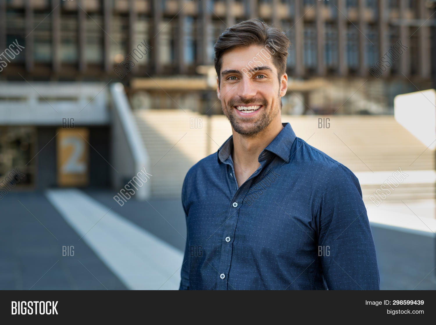 Portrait of happy young man in casual clothing looking at camera outdoor. Smiling man with beard feeling confident. Successful business man in city street.