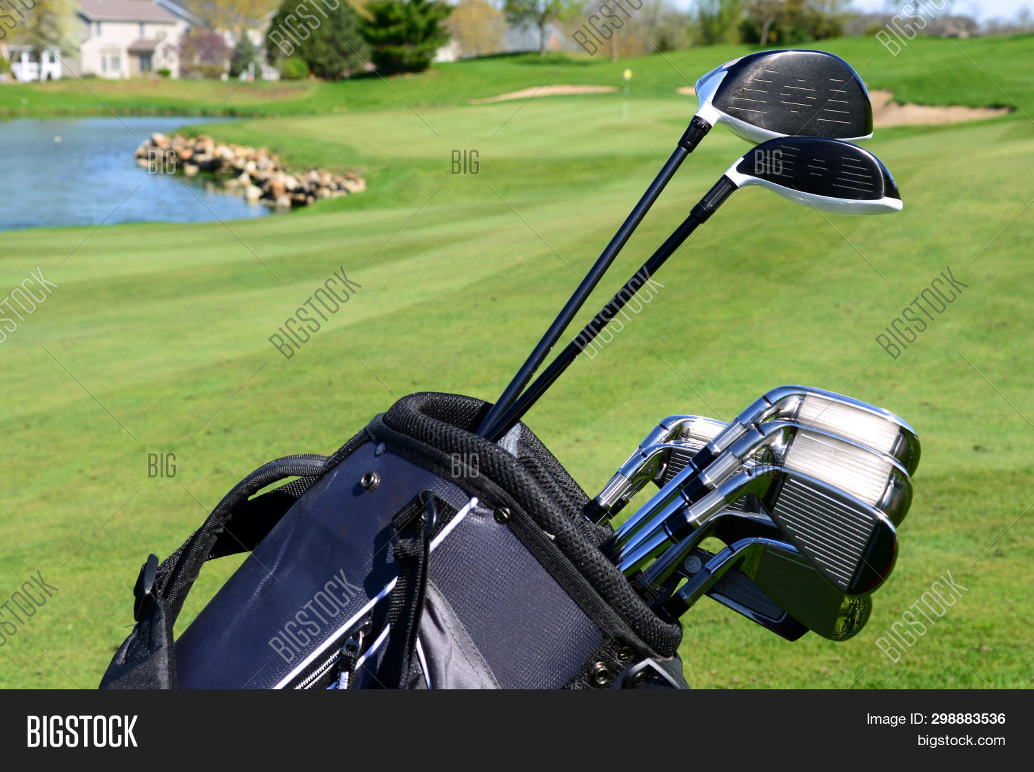 A set of golf clubs standing in a fairway on a scenic golf course with a lake and the green behind t