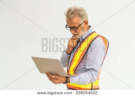 Experienced senior foreman or engineer using laptop computer standing against white background. Construction and engineering concept. stock photo