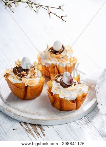 Easter Filo Pastry Baskets with meringue and melted chocolate and chocolate eggs on a white rustic background. Space for your text. stock photo