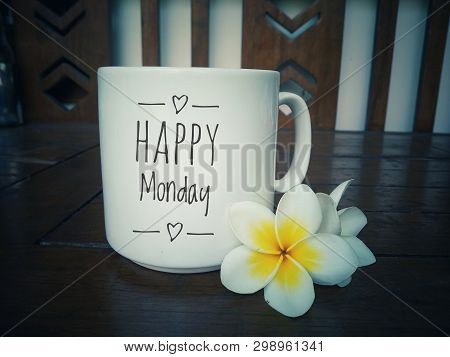 White mug of coffee with Happy Monday text design on it and beautiful Balinese frangipani flowers arrangement. Happy Monday! Have a productive week ahead. stock photo