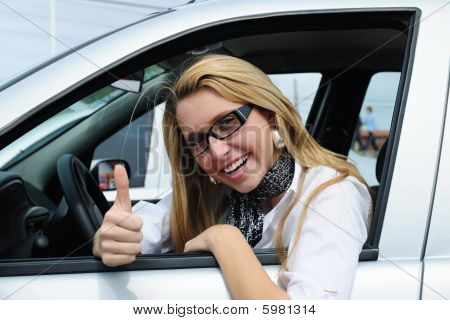 happy woman driving a new car giving thumbs up sign stock photo