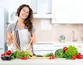 Young Woman Cooking in the kitchen. Solid Food - Vegetable Salad. Diet. Eating less Concept. Solid L