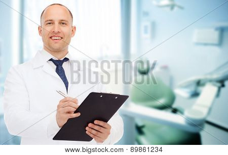 medicine, profession, stomatology and healthcare concept - smiling male dentist with clipboard writi