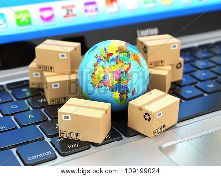 Shipping, delivery and logistic concept. Earth and cardboard boxes on laptop keyboard. Online techno