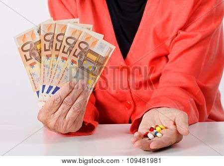 A senior woman paying money for medication stock photo