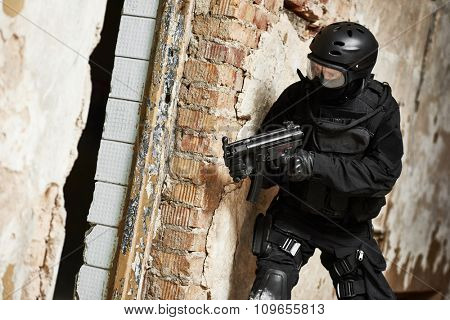 Military industry. Special forces or anti-terrorist police soldier, private military contractor armed with machine gun ready to attack during clean-up operation stock photo