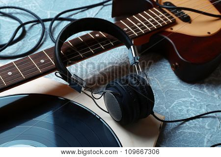 Electric guitar and headphones with music accessories on grey background stock photo