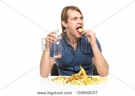 male slut drinking soda and eating chips. desk cesspool stock photo