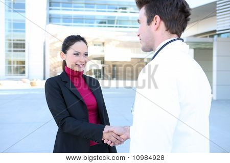 A man doctor and woman patient shaking hands outside hospital stock photo