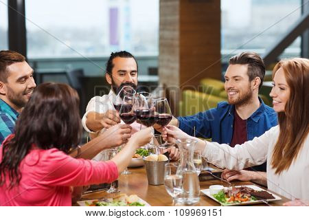 leisure, celebration, food and drinks, people and holidays concept - smiling friends having dinner a