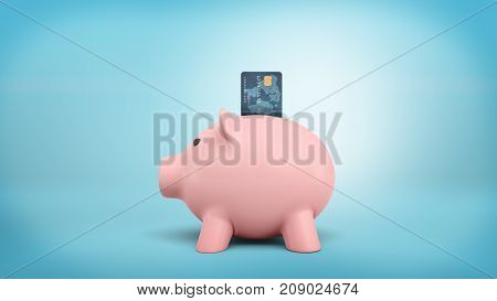 3d rendering of a pink piggy bank stands in a side view on a blue background with a credit card stuck into its coin slot. Cash against plastic cards. Saving money. Retail banking. stock photo