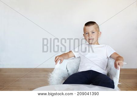 Picture of handsome blue eyed schoolboy with stylish haircut sitting in white chair in his room in confident posture thinking that he is special and unique his look expressing arrogance and conceit stock photo