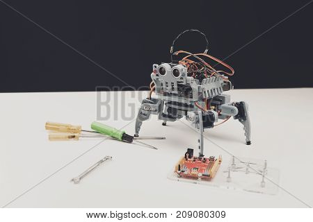 Robot close up. The robot is on the table. Next to him on the table are tools for assembling the robot