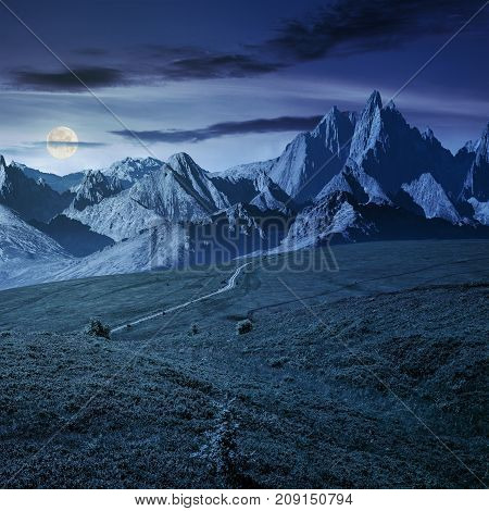 grassy slopes and rocky peaks composite. gorgeous summer landscape with magnificent mountain ridge over the pleasing green meadows. lovely surreal fantasy scenery at night in full moon light stock photo