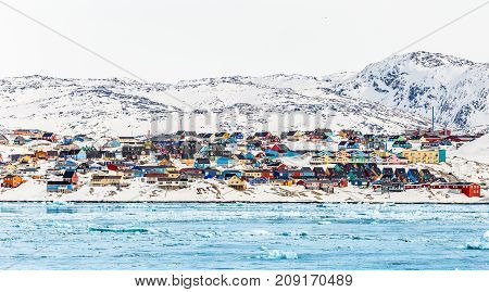 Arctic city panorama with colorful Inuit houses on the rocky hills covered in snow with snow and mountain in the background and blue icebergs in a foreground Ilulissat Greenland stock photo
