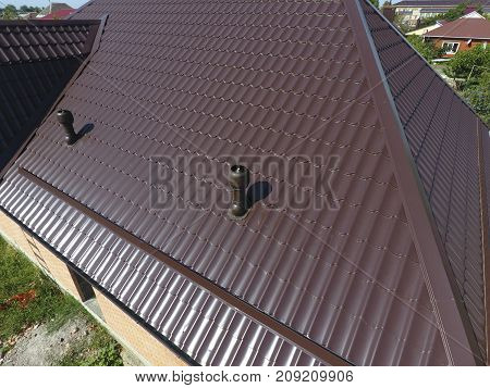 The roof of corrugated sheet. Roofing of metal profile wavy shape. Air ducts on metal roof. stock photo