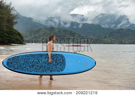 Stand up paddleboard fit man carrying paddle board going on ocean swim watersport activity at Puu Poa beach, Hanalei Bay, Kauai, Hawaii, USA. Hawaii travel sport athlete. stock photo