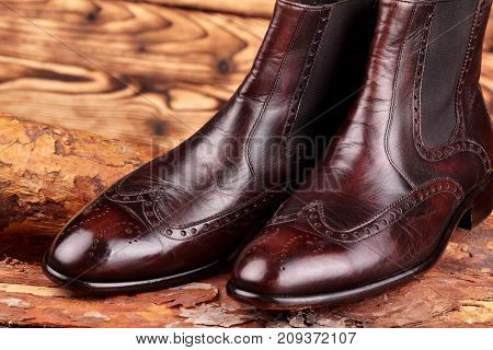 Brown leather chelsea boots polished on pine board. Waxing boots.Copy space.Closeup stock photo