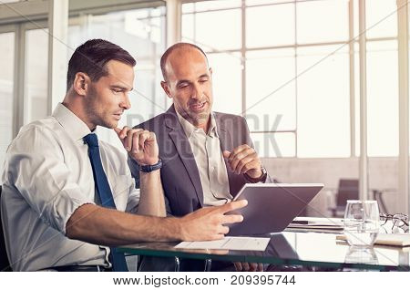 Businessman using a digital tablet to discuss information with senior leadership in a meeting. Busin