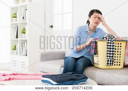 young elegant housewife making housekeeping feeling tired and getting headache painful when she folding clothing in living room. stock photo