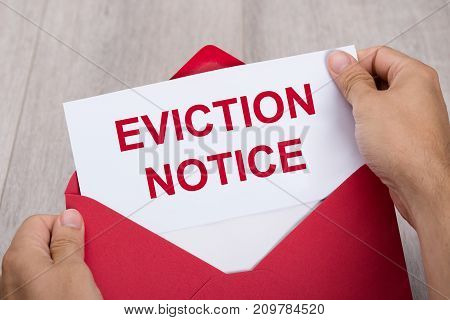 Close-up Of A Person's Hand Holding Eviction Notice In Red Envelope stock photo
