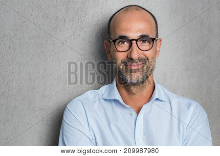 Portrait of a mature businessman wearing glasses on grey background. Happy senior latin man looking