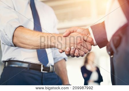 Businessmen shaking hands during a meeting. Closeup of business handshake between two colleagues in