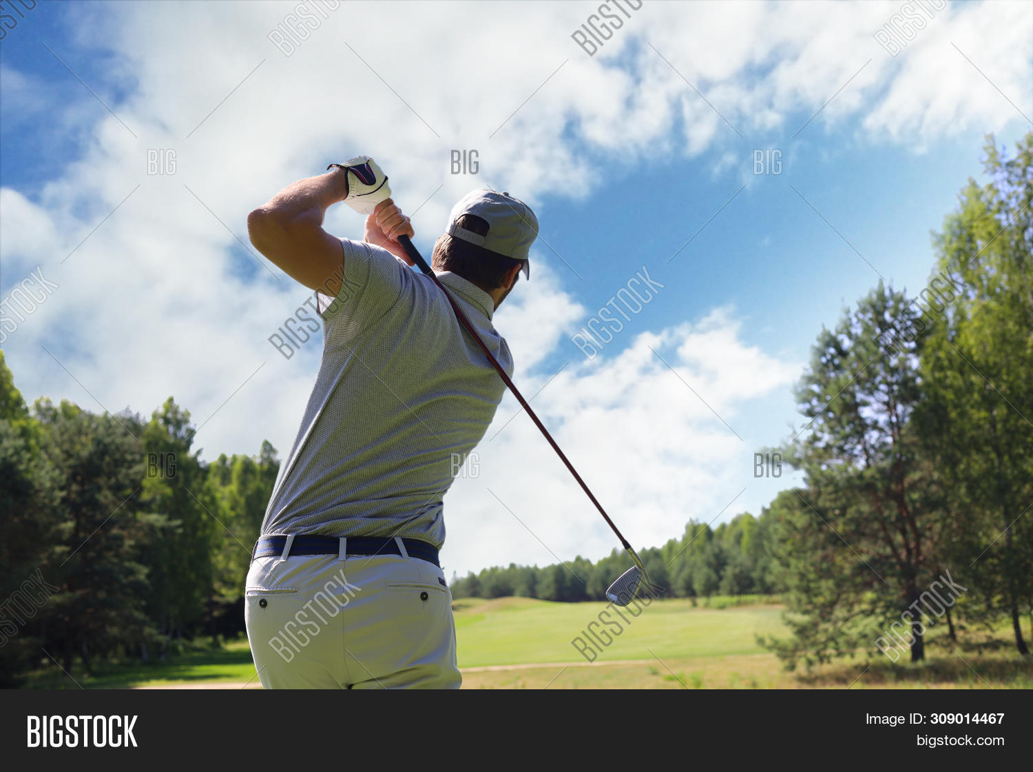 Golfer Hitting Golf Shot With Club On Course While On Summer Vacation.