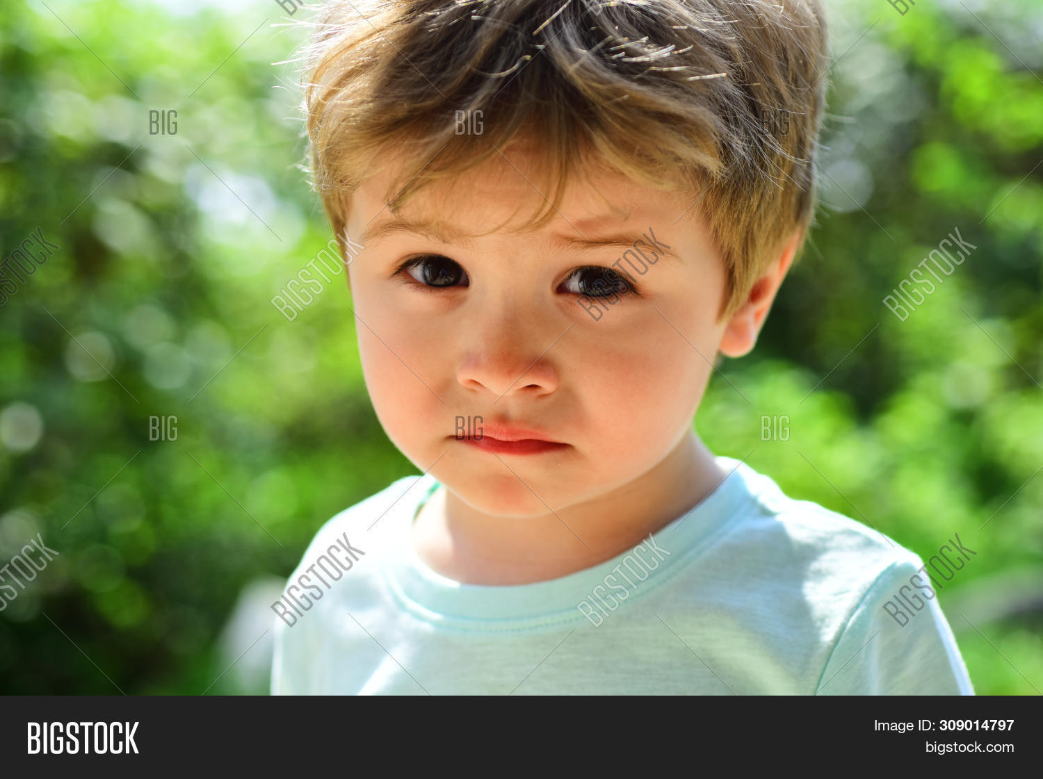 Sad child, close-up portrait. A frustrated child without mood. Sad emotions on a beautiful face. Child in nature. Fatigue after a walk. Sad childish look, disappointment in the eyes.