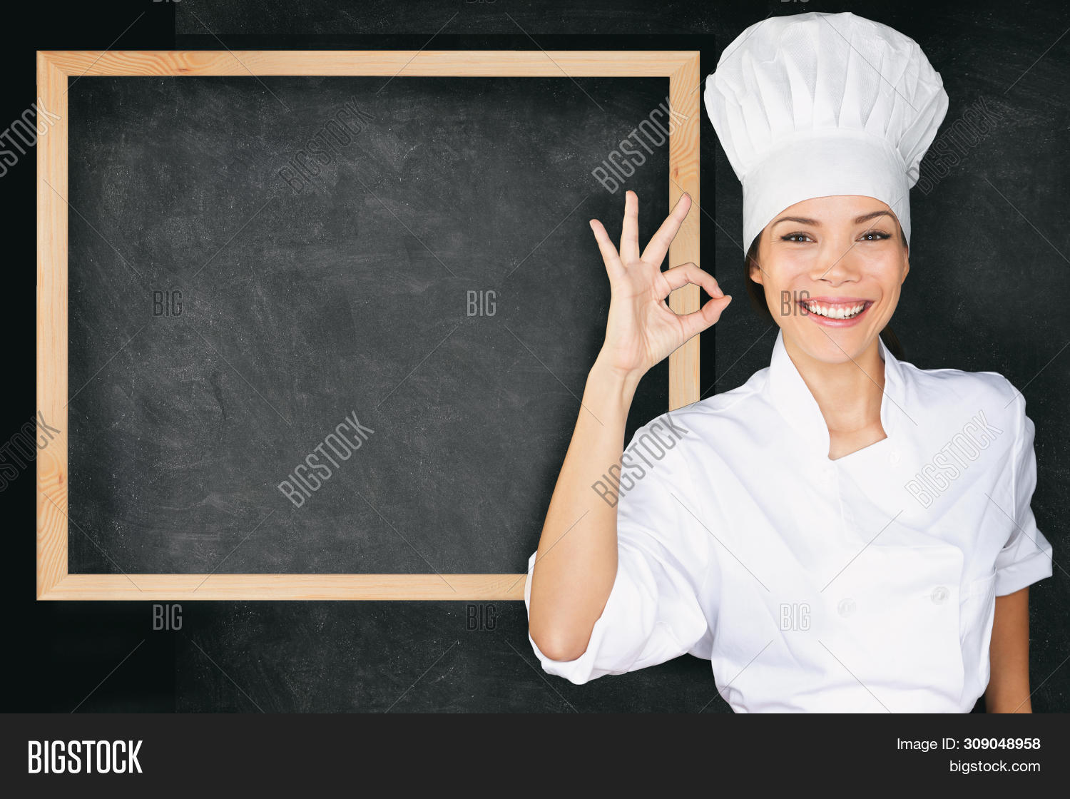 Happy chef doing perfect okay hand sign at empty menu black board background. Asian woman in front o