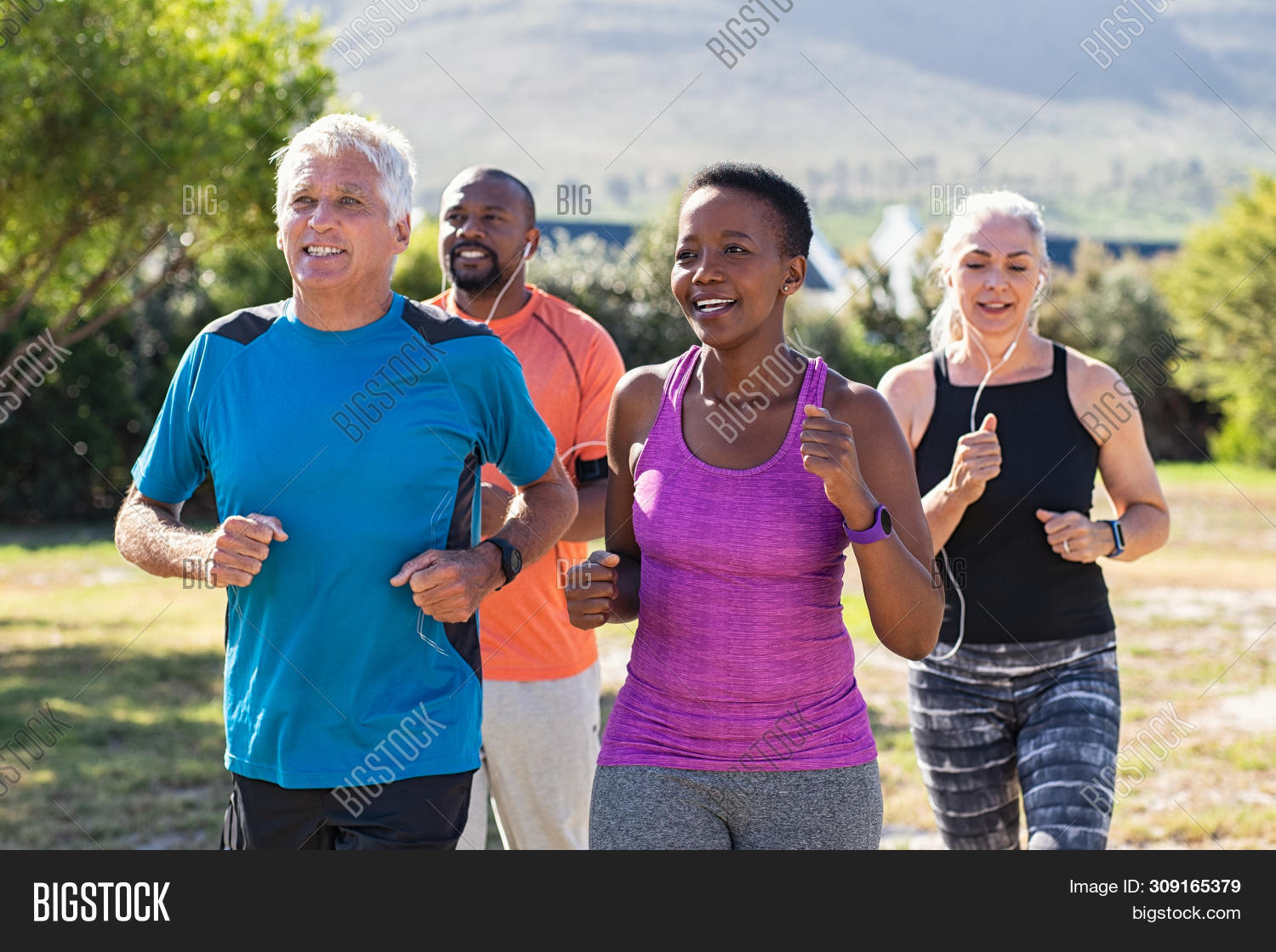 Healthy group of mature people jogging on track at park. Happy senior couple running at park with af