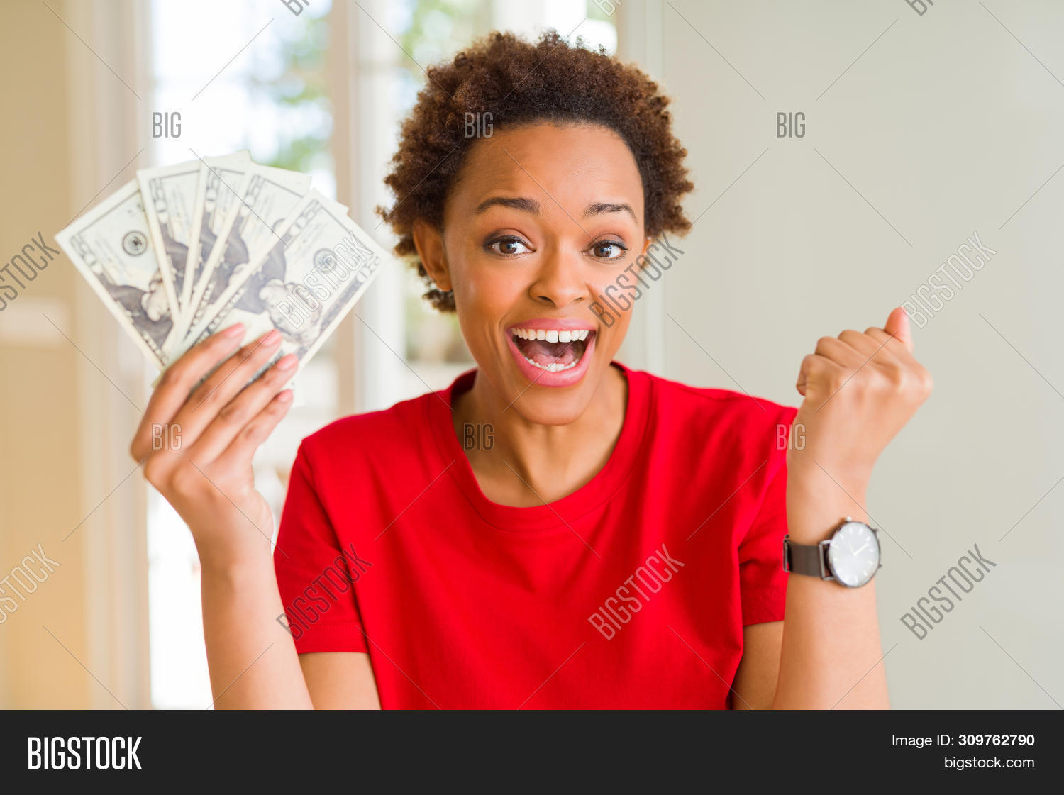 Young african american woman holding bank notes of twenty dollars screaming proud and celebrating vi