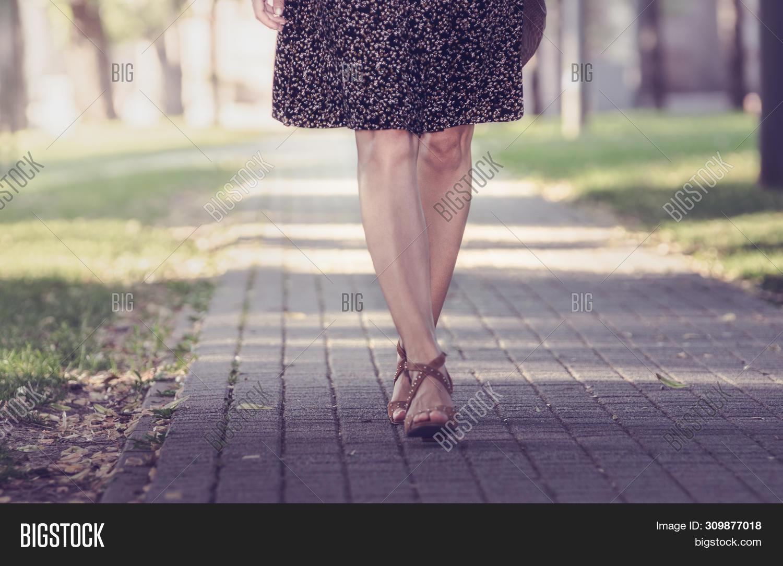 Woman legs walk in the Park. Woman legs walk in the park in brown shoes. Woman legs from the front. Close up of woman legs walking in park. Woman. Legs. Female legs. Sexy legs. Walk in the park.
