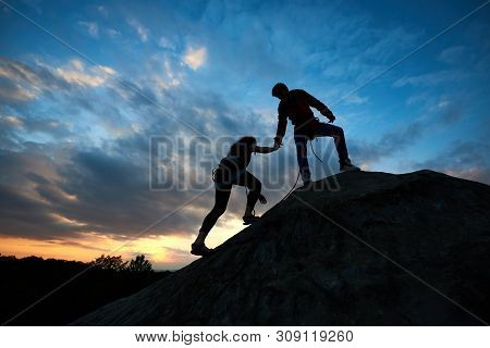 Silhouettes of two climbers reaching summit, one holding hand of partner assisting to make last step to top. Young man and woman athletes bouldering on high rock. Amazing sky and sunset on background. stock photo
