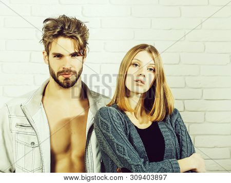 Young couple of handsome man or muscular macho in unzipped jacket with pretty cute girl or beautiful woman in knitted coat on white brick background stock photo