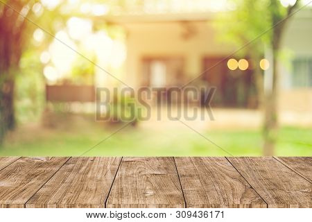 wooden table space with green home backyard view blur background for advertising template stock photo