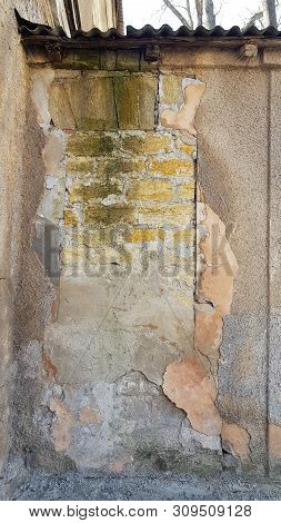 Dilapidated wall of abandoned building with layers of flaking stucco plaster layers and ancient brick masonry underneath. Brickwork surface covered with green moss. Grunge texture. Abstract background stock photo