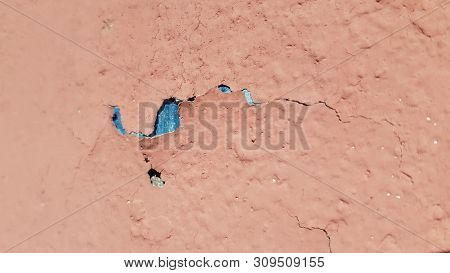 Abstract background of damaged painted surface closeup with flaking coral paint and blue paint underneath. Cracked backdrop of scratched and peeling paint cover of old rough wall. Grunge textures. stock photo