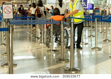 Caretaker with senior woman on wheelchair checkin in the airport. stock photo