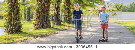 BANNER, LONG FORMAT Boy and girl on kick scooters in park. Kids learn to skate roller board. Little boy skating on sunny summer day. Outdoor activity for children on safe residential street. Active sport for preschool kid stock photo