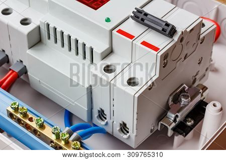 Double input automatic circuit breaker and voltage limiter closeup in the white plastic mounting box stock photo