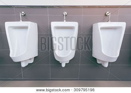 Men's room with white porcelain urinals in line. Modern clean public toilets with tiles . Comfort male toilet urinal concept. stock photo